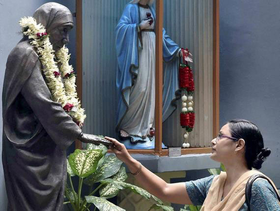 devotee before a statue of Mother Teresa